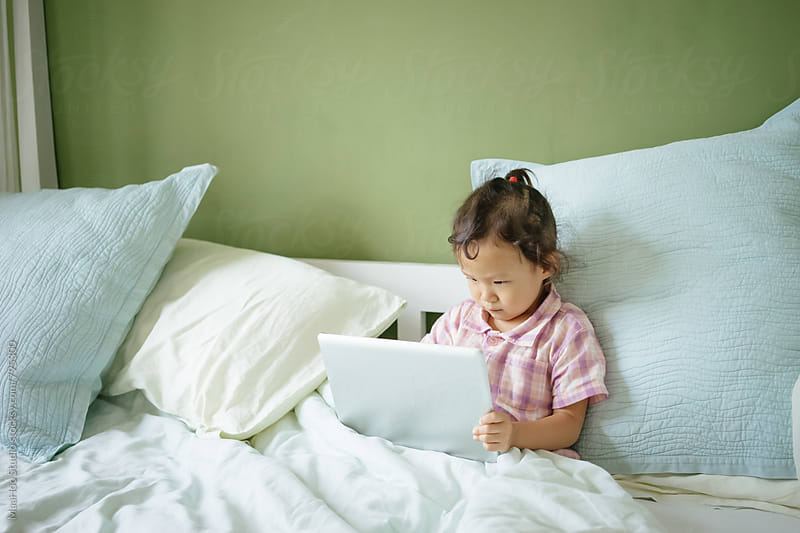 Toddler girl using digital PC on bed by Maa Hoo for Stocksy United