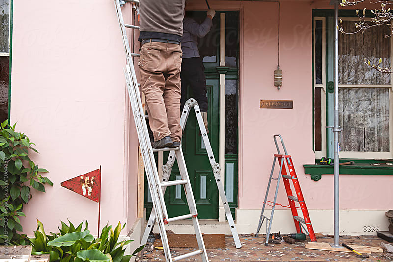 front exterior of a home undergoing renovation / repair by Natalie JEFFCOTT for Stocksy United