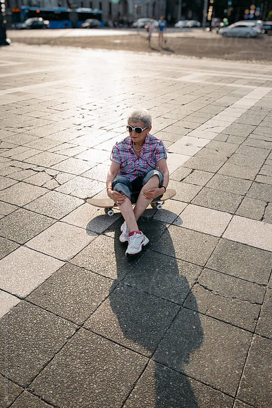 Backlit senior woman sitting on a skateboard waiting for her grandkids by Beatrix Boros for Stocksy United