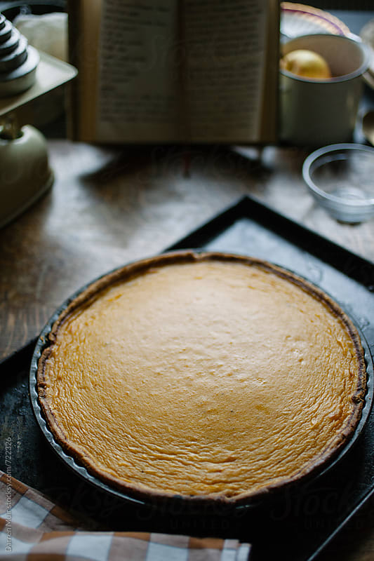 Freshly baked pumpkin pie on oven tray. by Darren Muir for Stocksy United