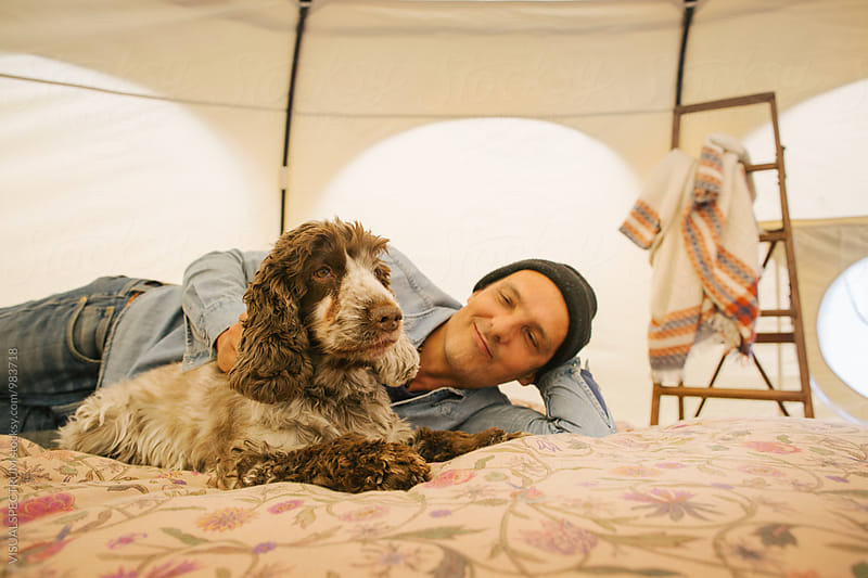 Glamping - Caucasian Man Stroking Cocker Spaniel on Bed Inside Large Circular Tent by Julien L. Balmer for Stocksy United