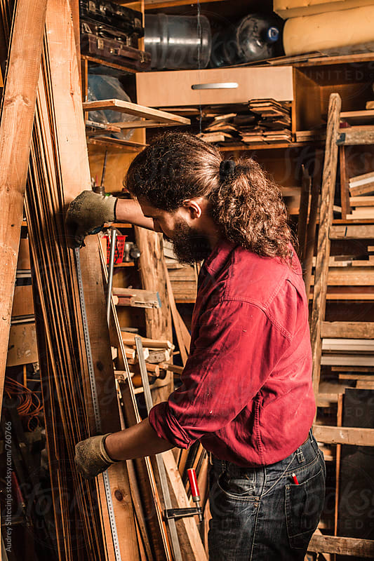 Male carpenter measuring wooden boards . by Marko Milanovic for Stocksy United