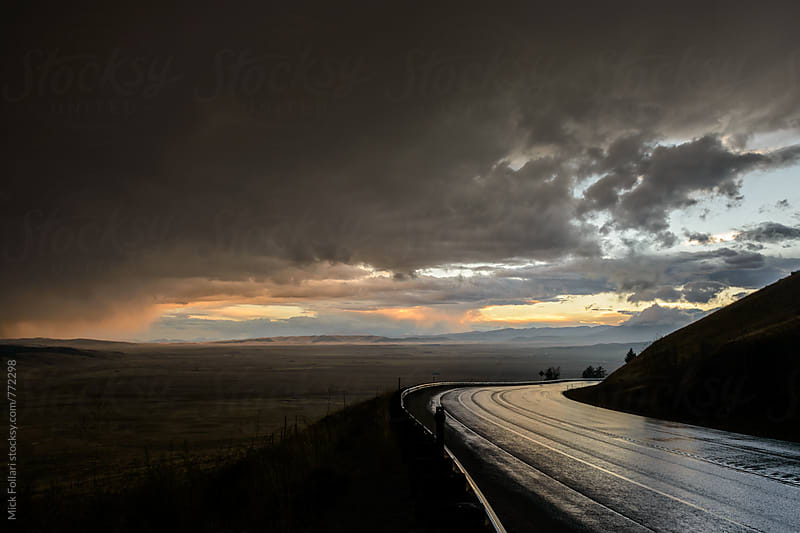Wet road with dramtic weather at sunset by Mick Follari for Stocksy United