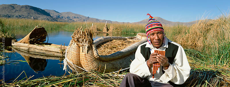 Portrait of a Uros Indian man holding pipes, on floating reed island, Islas Flotantes, Lake Titicaca by Gavin Hellier for Stocksy United