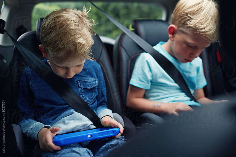 Children using electronic tablets while sat in the car by sally anscombe for Stocksy United