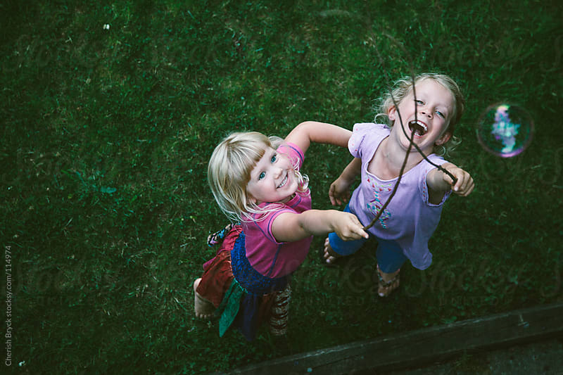 two little girls try play with bubbles. by Cherish Bryck for Stocksy United