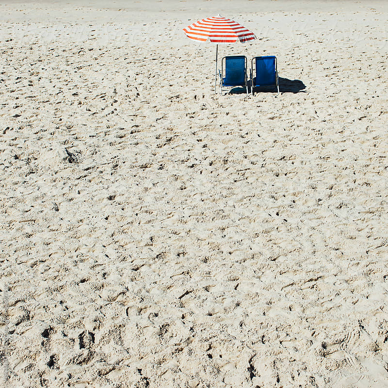 Two Beach Chairs and Striped Umbrella on Empty Sunny Beach by VISUALSPECTRUM for Stocksy United