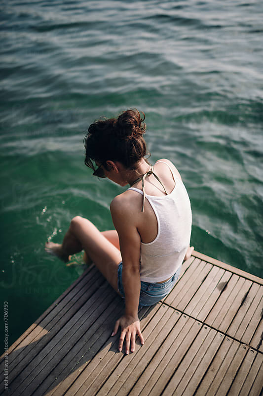 Young woman dangling her feet on the lake by michela ravasio for Stocksy United