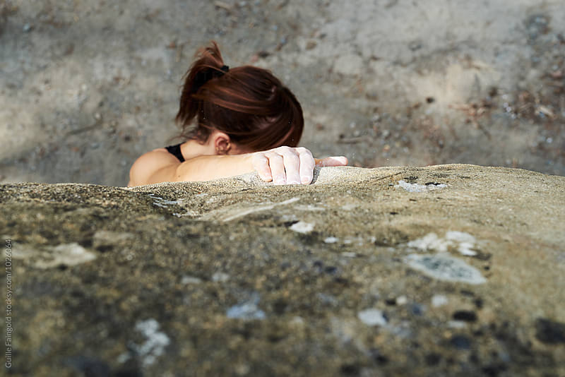 Brunette climbing the rock with hand in talc by Guille Faingold for Stocksy United
