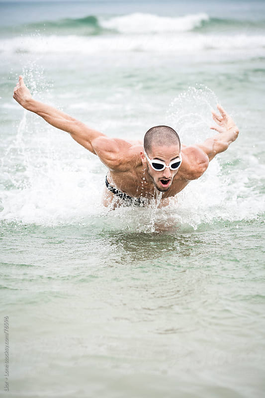 Athlete doing butterfly strokes at sea by Lior + Lone for Stocksy United