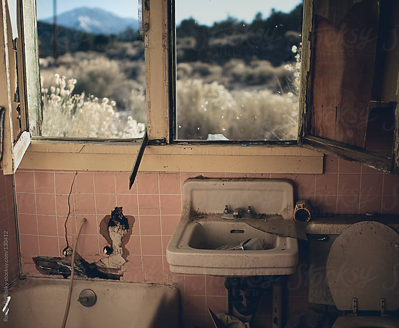 An abandoned and vandalized bathroom with a majestic desert view by Rachel Bellinsky for Stocksy United