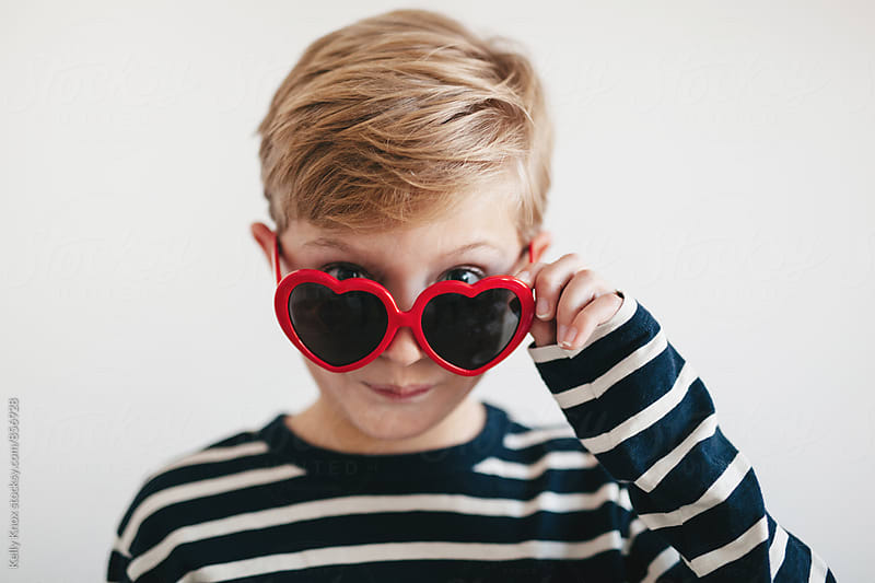 cute boy looking over valentine's sunglasses by Kelly Knox for Stocksy United