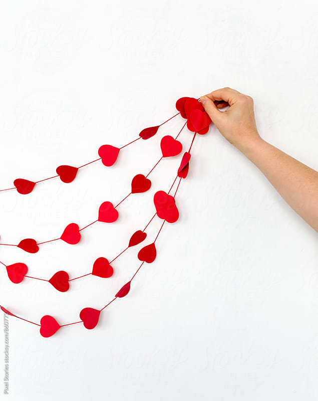 Woman hanging handmade heart garland by Pixel Stories for Stocksy United