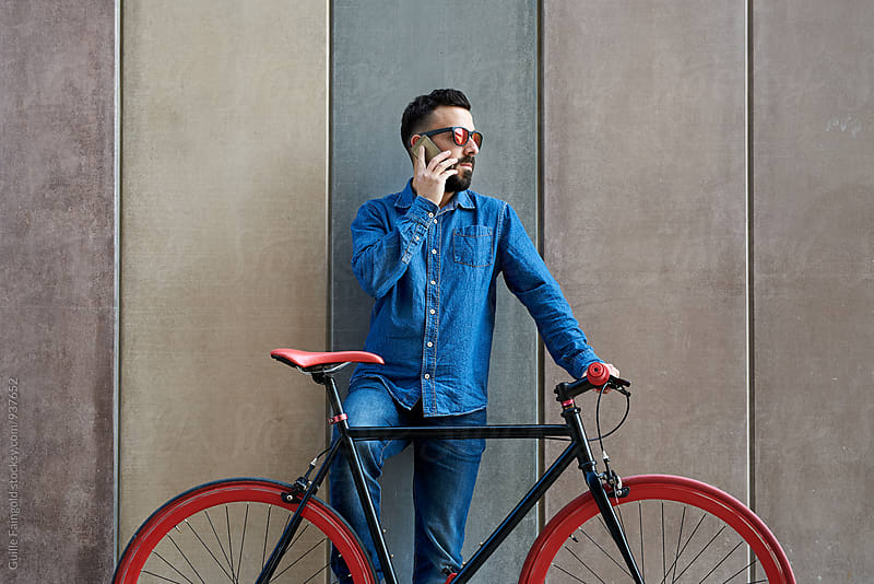 Young man on fixed gear bicycle using his smartphone by Guille Faingold for Stocksy United