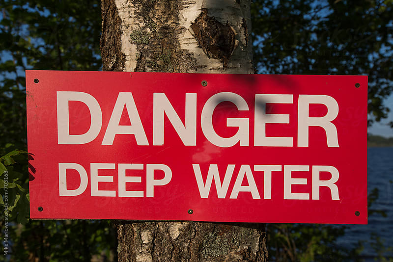 A sign in red warning of danger of deep water by Mike Marlowe for Stocksy United