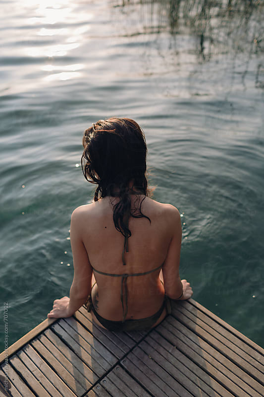Woman relaxing on the pier at sunset by michela ravasio for Stocksy United