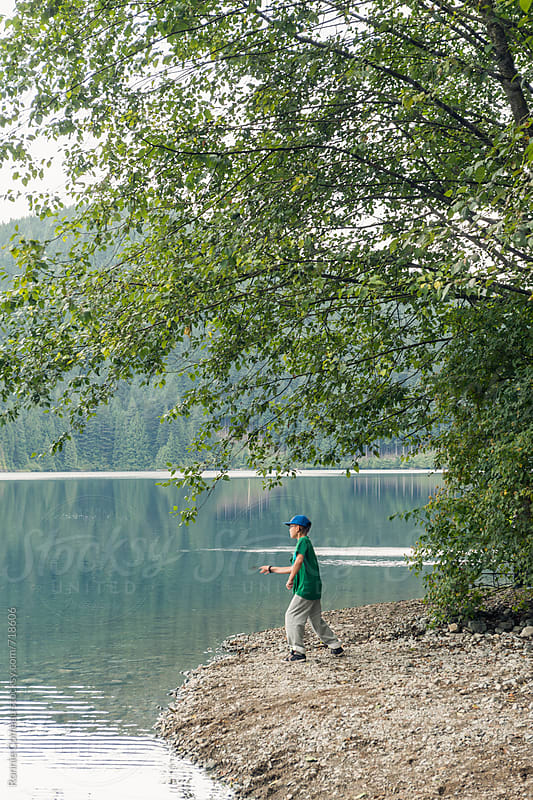 Boy Skipping Rock At Lake by Ronnie Comeau for Stocksy United