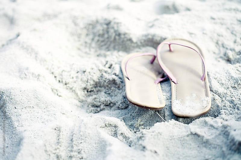 Light pink flip flops in the sand by Carolyn Lagattuta for Stocksy United
