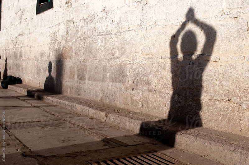 Pray time silhouette,  on old Tibettan building by Caine Delacy for Stocksy United
