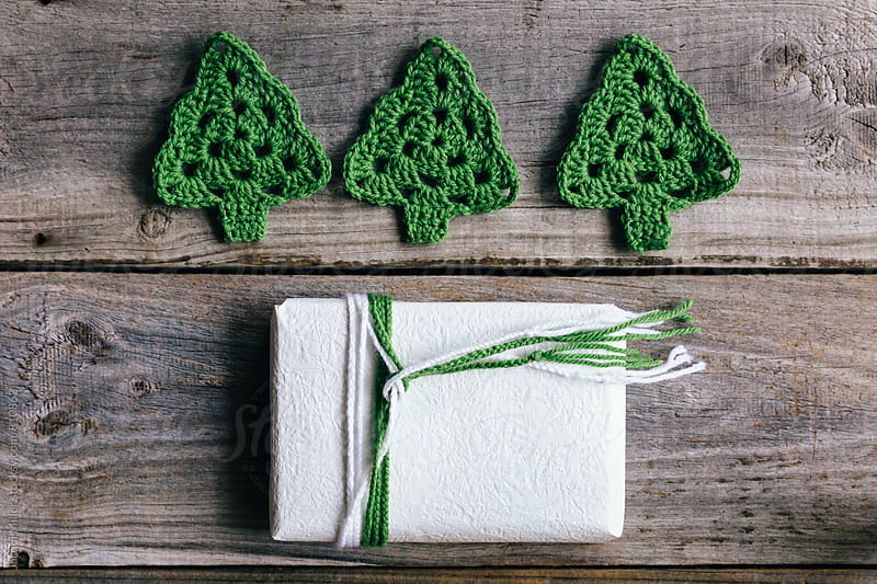 Simple Christmas gift tied with plaited wool, with crocheted Christmas Trees, horizontal by Jacqui Miller for Stocksy United