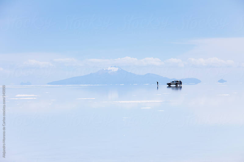 Salar de Uyuni salt flat view with all terrain vehicle reflection and mountains on the background. by Alejandro Moreno de Carlos for Stocksy United