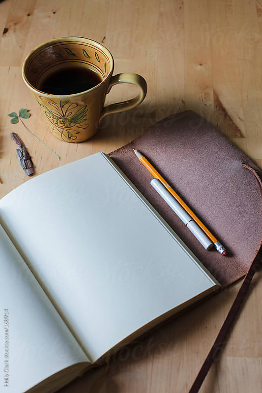 A blank journal lies open on a table next to a cup of coffee, a pencil and an e-cigarette. by Holly Clark for Stocksy United