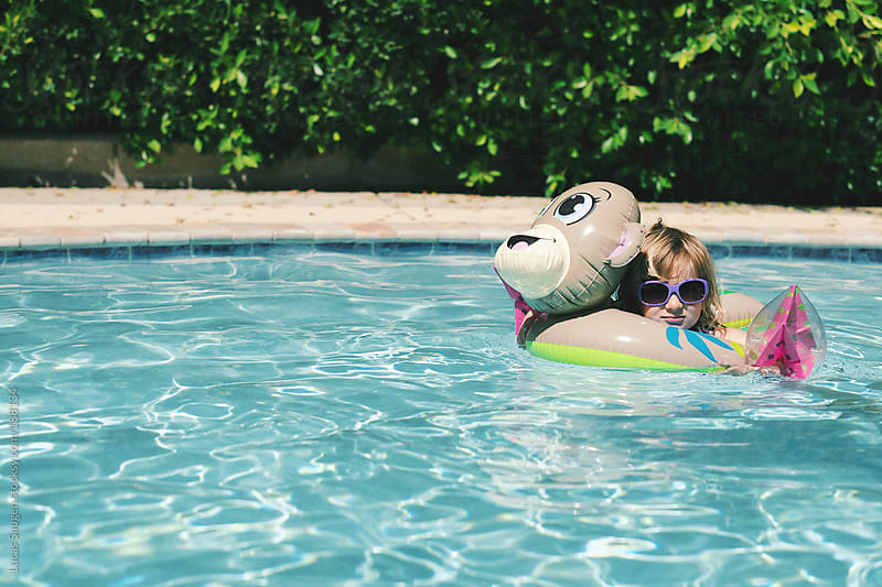 Young girl swims in a pool with her inflatable toys. by Lucas Saugen for Stocksy United
