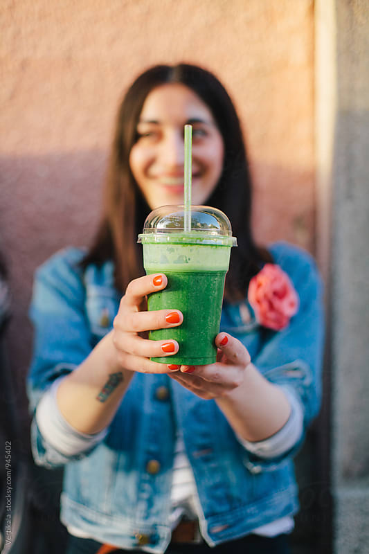 Woman holding green smoothie  by Marija Mandic for Stocksy United