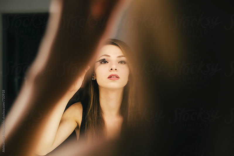 Beautiful woman making her face infrot of the mirror by Aleksandar Novoselski for Stocksy United