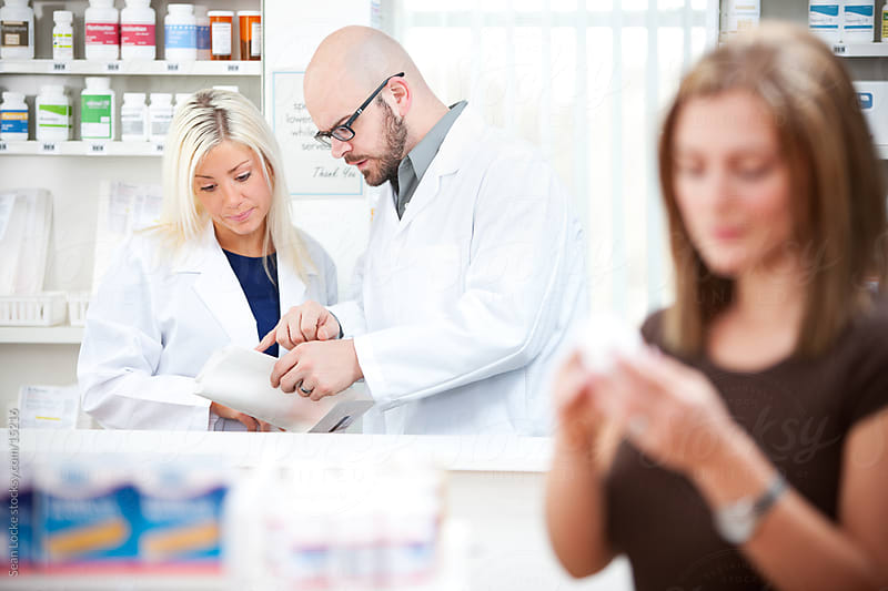 Pharmacy: Pharmacists Discuss Prescription Behind Counter by Sean Locke for Stocksy United