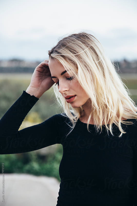 Beautiful blonde female wearing black by Curtis Kim for Stocksy United