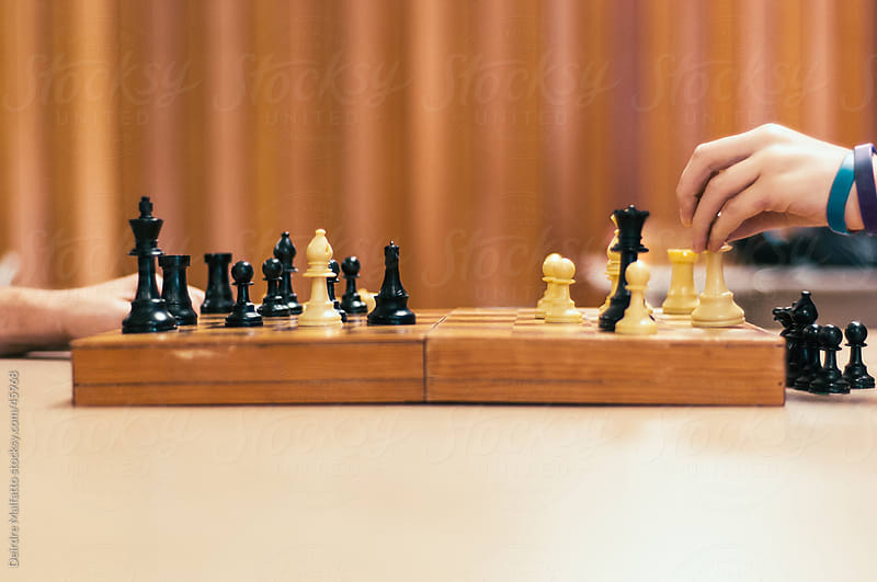 Hands playing chess on a wooden board by Deirdre Malfatto for Stocksy United