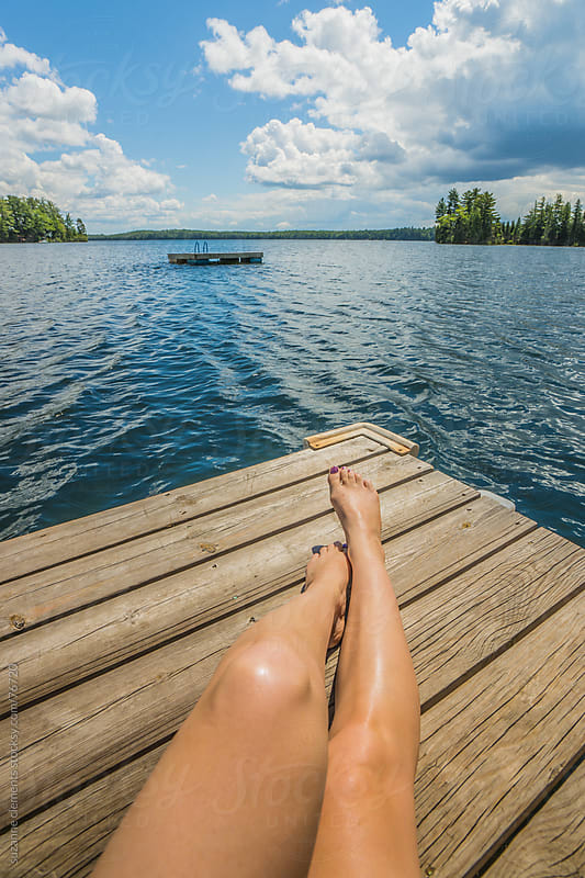 Woman Sunbathes on a Warm Summer Day by a Lake by suzanne clements for Stocksy United