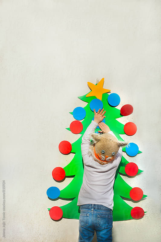 Decorate a Christmas tree by Jelena Jojic Tomic for Stocksy United