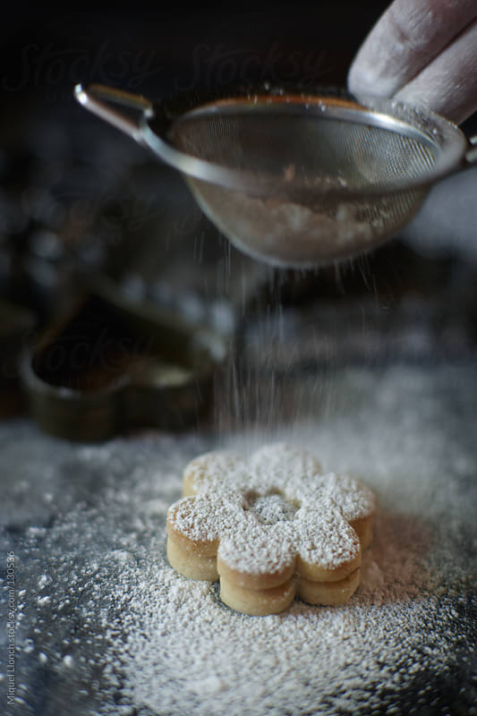 Sugar dusting on a cookie by Miquel Llonch for Stocksy United