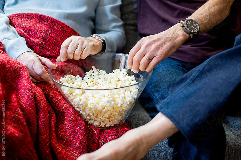 Closeup of an elderly couple eating popcorn at home. by BONNINSTUDIO for Stocksy United