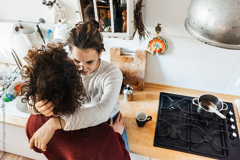 Young people hugging each other in a kitchen. by minamoto images for Stocksy United