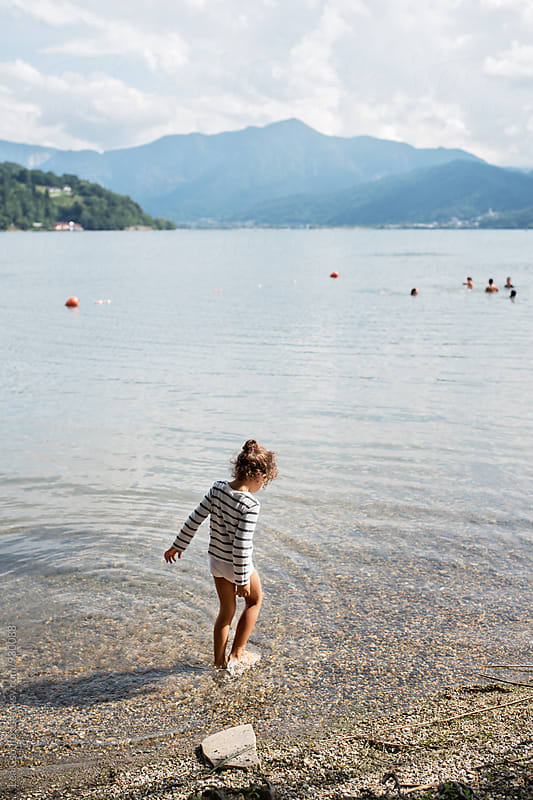 Little girl walking into a lake by Lea Csontos for Stocksy United