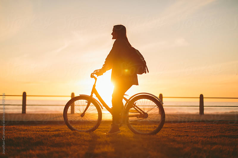 Beautiful woman girl riding bicycle on grass lawn overlooking the ocean at sunrise or sunset  by Jonathan Caramanus for Stocksy United