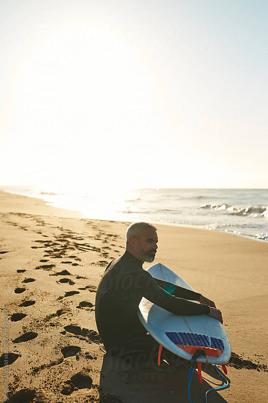 Portrait of serious bearded man with surfboard by Guille Faingold for Stocksy United