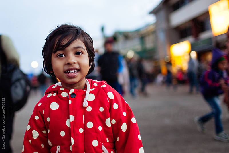 Cute little girl smiling standing on the street in a winter evening by Saptak Ganguly for Stocksy United