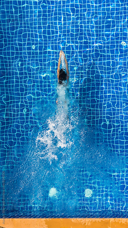 Young woman in swimming under water  in the pool/look form above. by Marko Milanovic for Stocksy United