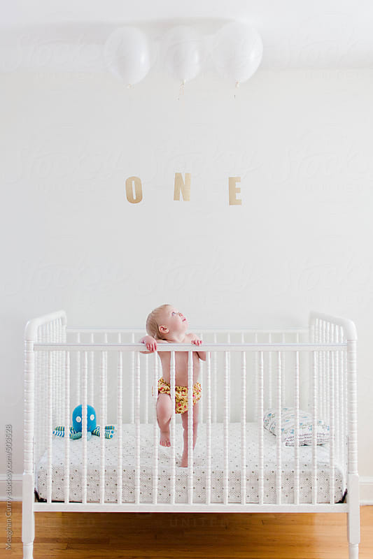 Cute baby standing in a crib on her first birthday with balloons and the word one by Meaghan Curry for Stocksy United