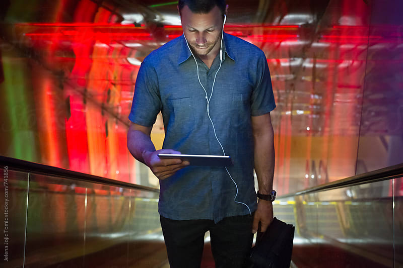 Man looks down on his tablet while standing at the elevator by Jelena Jojic Tomic for Stocksy United