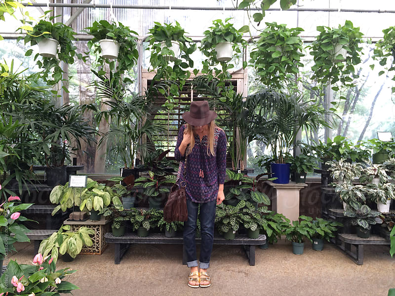 A woman stands in a greenhouse surrounded by plants. by Kelsey Gerhard for Stocksy United