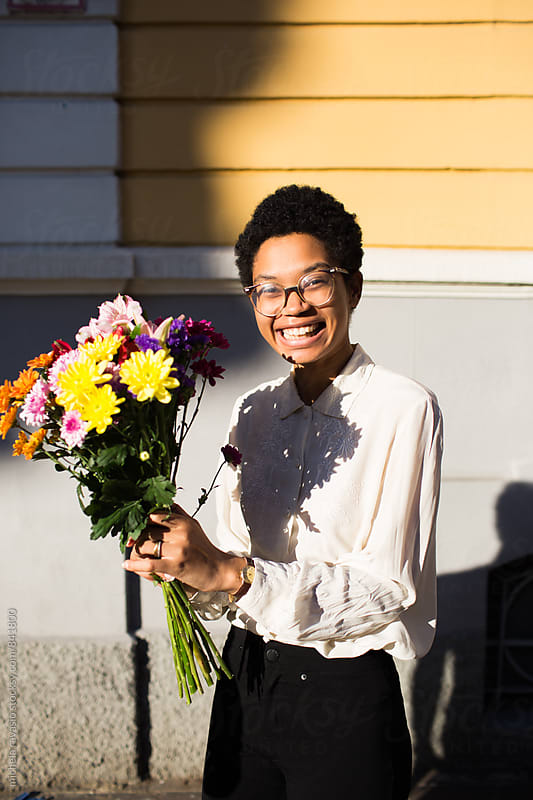 Happy woman holding a bouquet of flowers by michela ravasio for Stocksy United