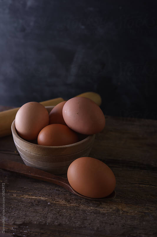 Fresh hens eggs in a bowl on a wooden table. by Darren Muir for Stocksy United