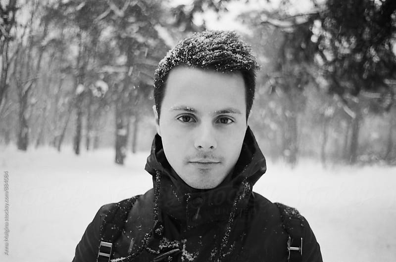 A black and white film portrait of young men with snow on his hair by Anna Malgina for Stocksy United