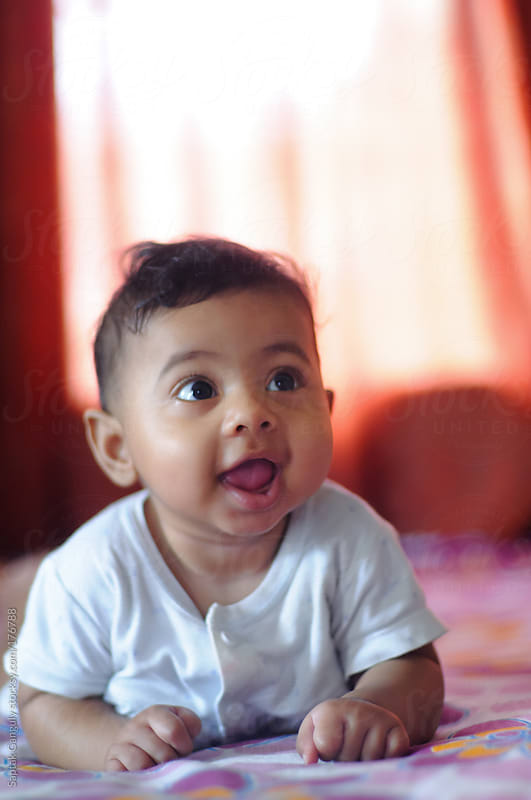 Cute baby girl lying on her front and smiling by Saptak Ganguly for Stocksy United