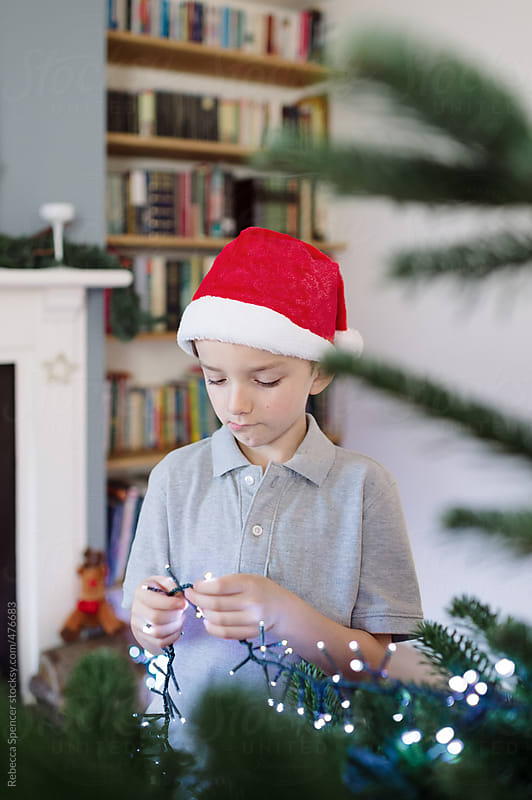 Santa hat clad child adding lights to Christmas tree by Rebecca Spencer for Stocksy United